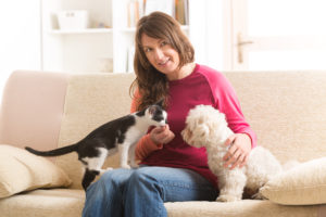Pet sitter with pets on sofa.